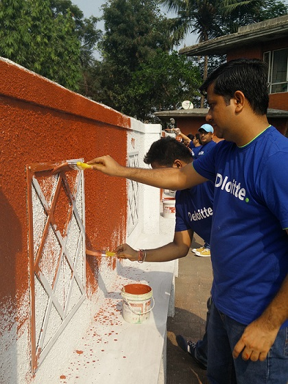 Deloitte employees helping with the painting at New Mumbai